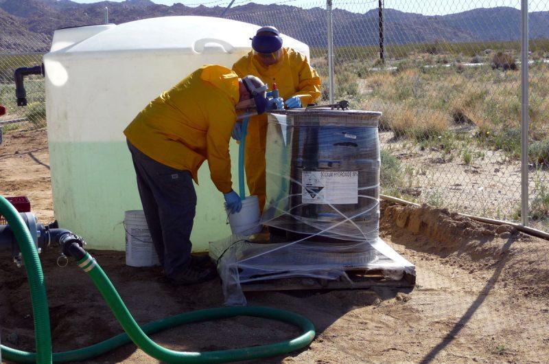 Regeneration team members prepare the caustic regeneration solution in the storage tank.